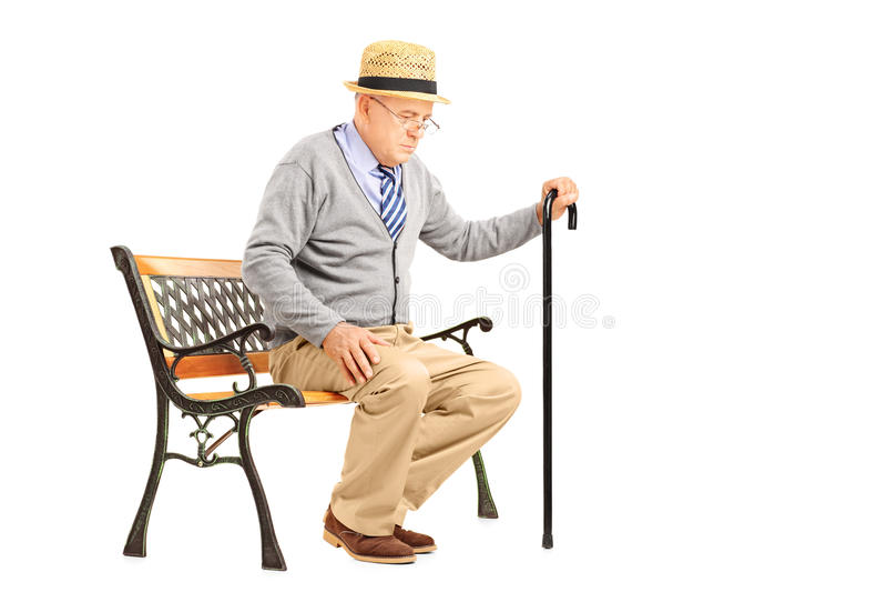 Uomo senior con una canna che si siede su un banco immagini stock libere da diritti