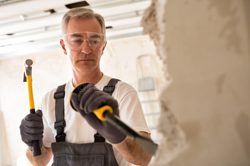 Uomo senior degno che lavorano con il martello e strumento mentre demolisca il wa fotografie stock