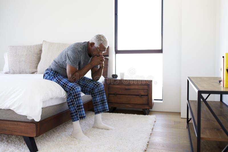 Uomo senior depresso che sembra seduta infelice dal lato del letto a casa con la testa in mani immagine stock