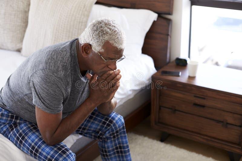 Uomo senior depresso che sembra seduta infelice dal lato del letto a casa con la testa in mani fotografia stock libera da diritti