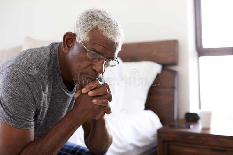 Uomo senior depresso che sembra seduta infelice dal lato del letto a casa con la testa in mani fotografie stock libere da diritti