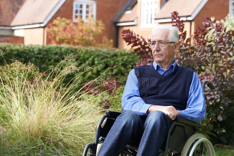 Uomo senior depresso che si siede all'aperto in sedia a rotelle fotografia stock libera da diritti