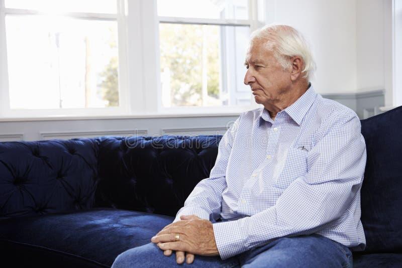 Uomo senior depresso che si siede su Sofa At Home fotografia stock