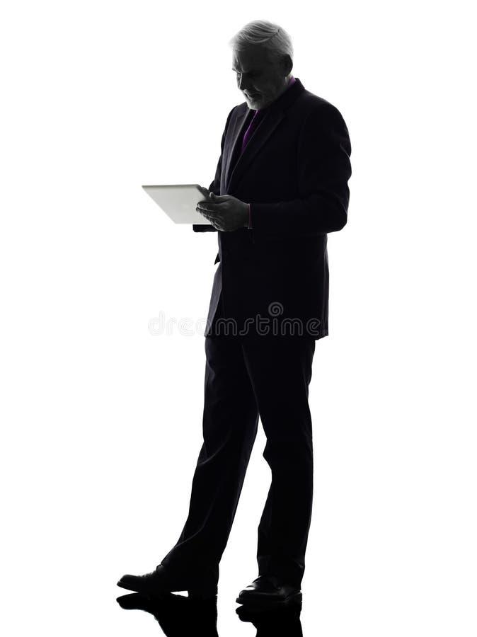 Uomo senior di affari che tiene la siluetta digitale della compressa immagini stock libere da diritti