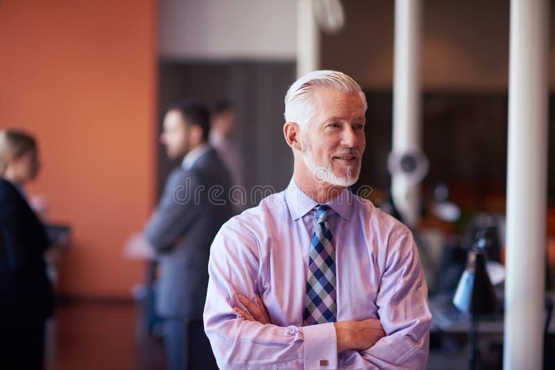 Uomo senior di affari con il suo gruppo all'ufficio fotografie stock