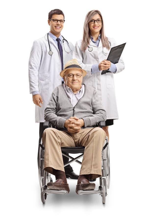 Uomo senior disabile in una sedia a rotelle ed in un medico femminile e del maschio che stanno dietro lui fotografia stock