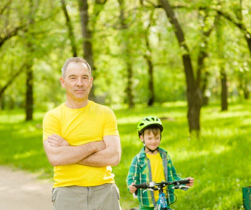 Uomo senior e bambino su una bicicletta nel parco immagini stock