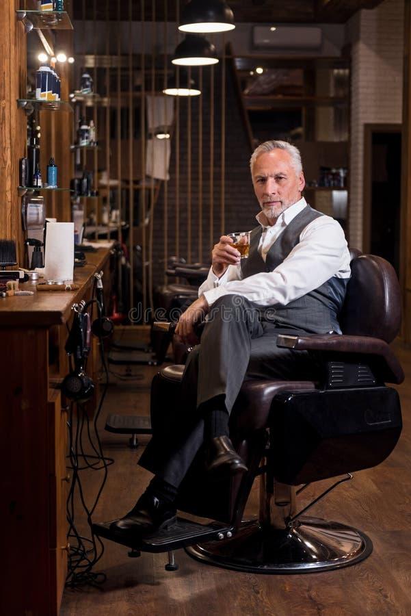 Uomo senior elegante con il vetro ed il sigaro del whiskey al parrucchiere fotografia stock libera da diritti