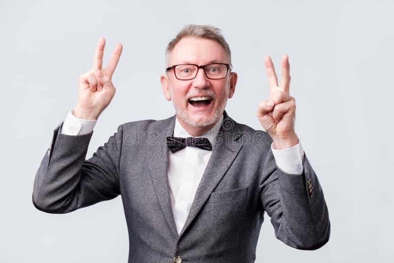 Uomo senior felice che fa il segno della mano di pace o di vittoria fotografia stock