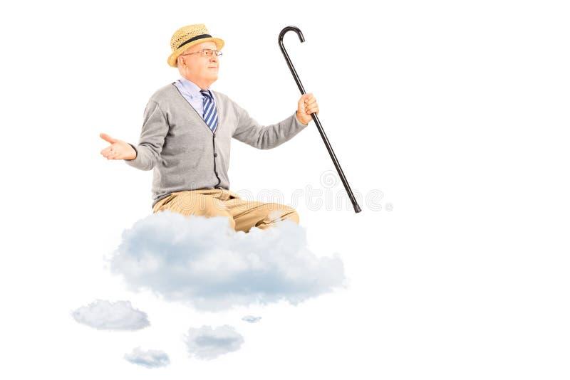 Uomo senior felice che galleggia su una nuvola e sulle armi di diffusione immagini stock libere da diritti