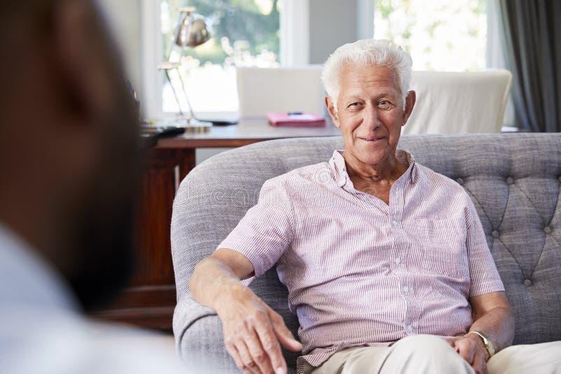 Uomo senior felice che prende consiglio finanziario a casa immagine stock libera da diritti