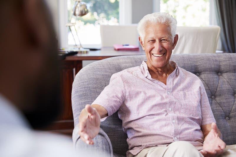 Uomo senior felice che prende consiglio finanziario a casa fotografia stock