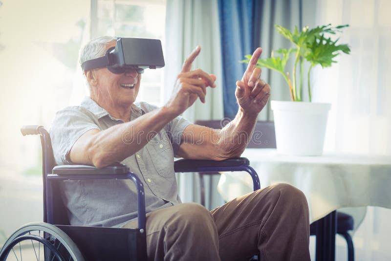 Uomo senior felice sulla sedia a rotelle facendo uso della cuffia avricolare di VR fotografia stock