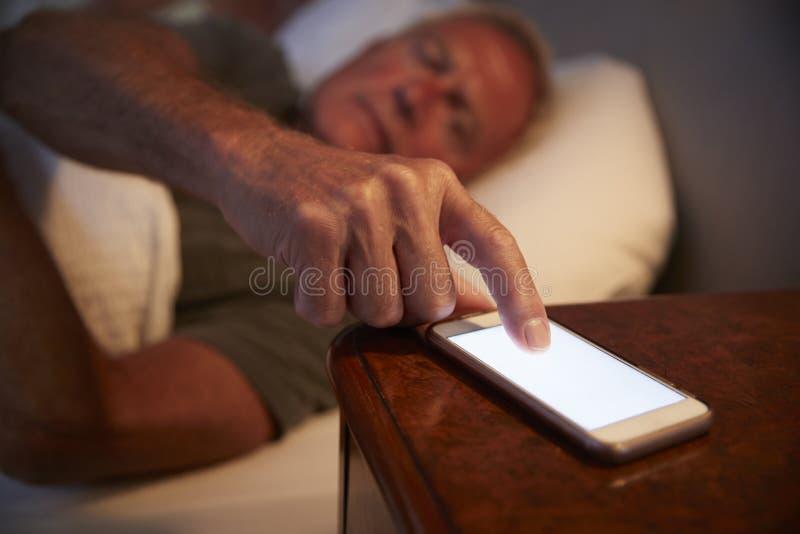 Uomo senior insonne a letto alla notte che controlla telefono cellulare fotografia stock libera da diritti