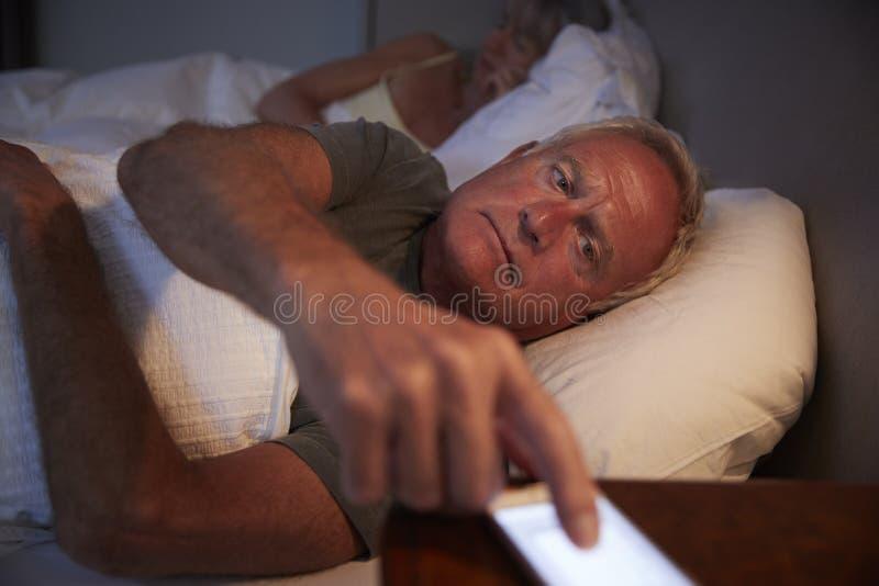 Uomo senior insonne a letto alla notte che controlla telefono cellulare fotografia stock