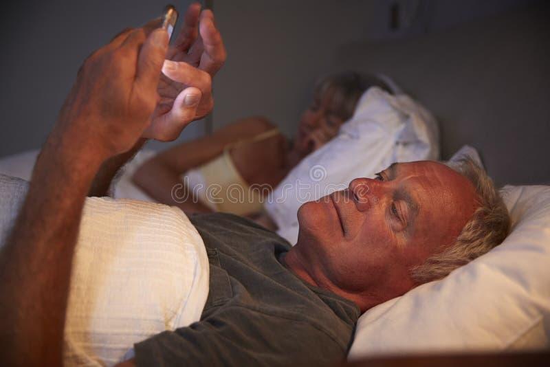 Uomo senior insonne a letto alla notte facendo uso del telefono cellulare immagini stock libere da diritti