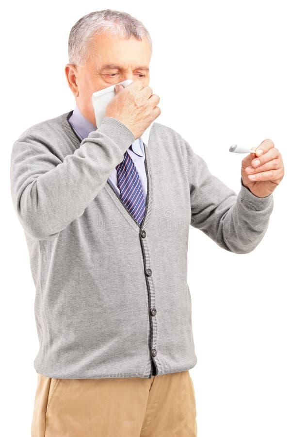 Uomo senior malato che soffia il suo radiatore anteriore in carta velina immagini stock