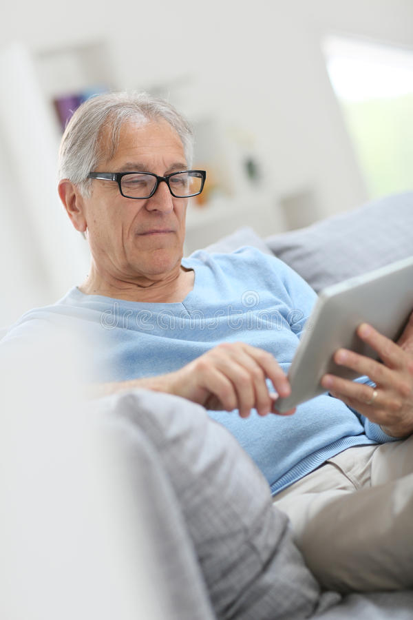 Uomo senior moderno che legge giornale digitale fotografia stock libera da diritti
