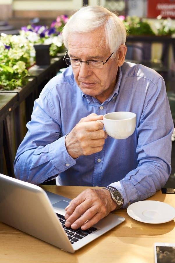 Uomo senior moderno che per mezzo del computer portatile alla pausa caffè immagini stock libere da diritti