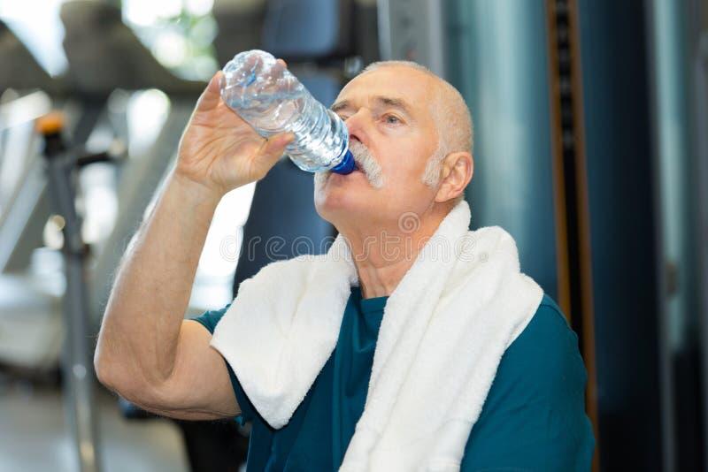 Uomo senior nel centro di forma fisica che beve dall'acqua di bottiglia fotografie stock