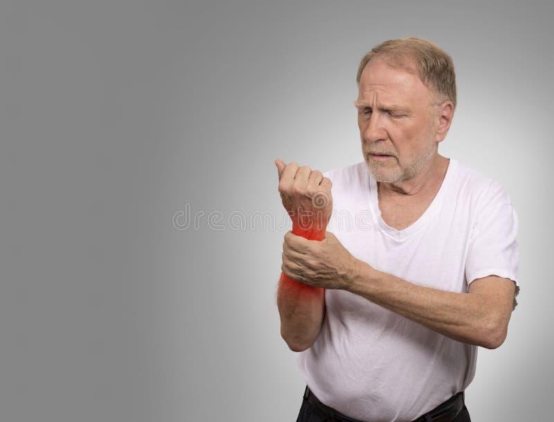 Uomo senior nell'artrite dolorosa del polso di dolore lancinante della mano immagine stock libera da diritti