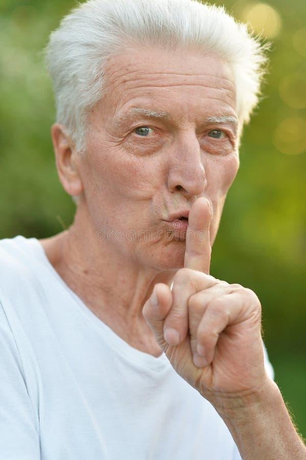 Uomo senior in parco con il gesto di silenzio fotografia stock libera da diritti
