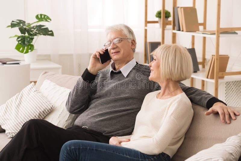 Uomo senior pensionato che parla sul telefono, avendo resto con la moglie fotografia stock libera da diritti