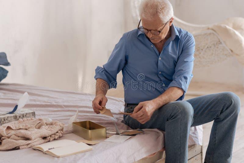 Uomo senior piacevole che controlla la sua vecchia posta fotografie stock