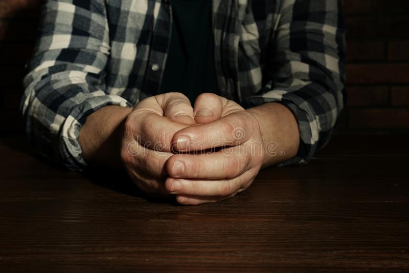 Uomo senior povero che si siede alla tavola immagini stock