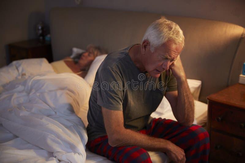 Uomo senior preoccupato a letto alla notte che soffre con l'insonnia fotografia stock