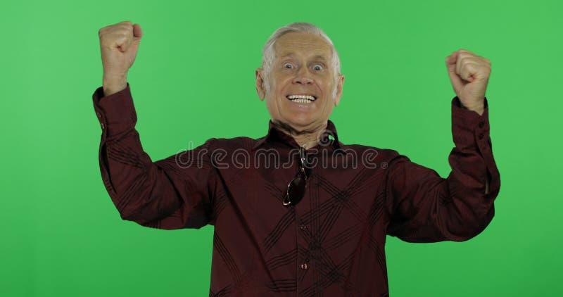 Uomo senior qualcosa che celebra emozionalmente Uomo anziano bello sulla chiave di intensità fotografie stock libere da diritti