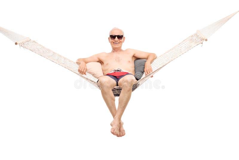 Uomo senior rilassato che si siede in un'amaca comoda immagine stock