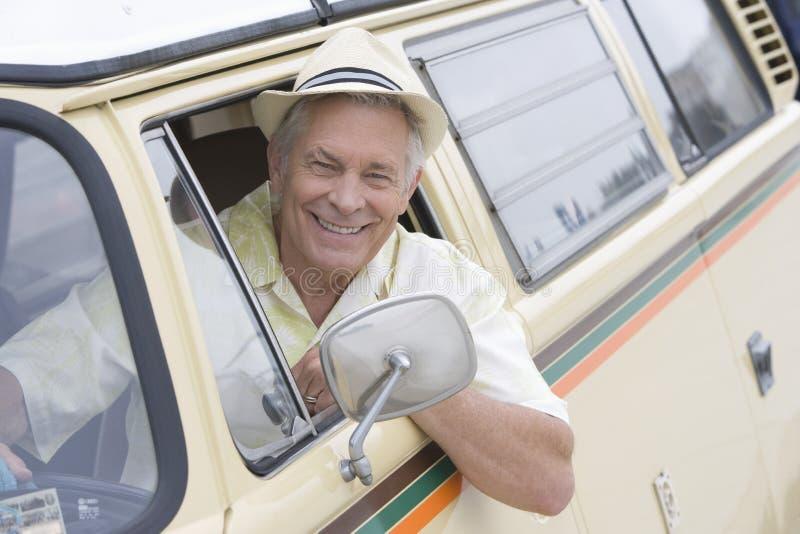 Uomo senior in Seat del driver di Campervan che guarda attraverso la finestra immagine stock