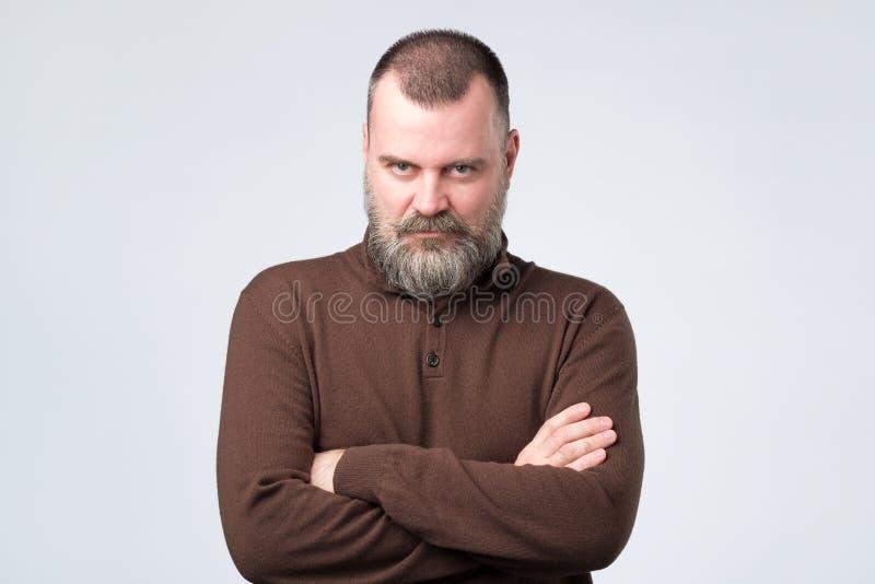 Uomo senior sicuro con la barba in mani d'attraversamento della maglietta marrone sul petto ed esaminare macchina fotografica immagine stock