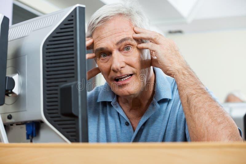 Uomo senior sollecitato durante la classe del computer immagini stock libere da diritti