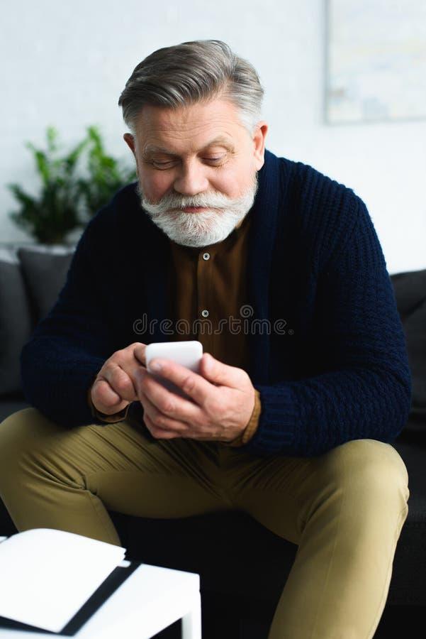 uomo senior sorridente bello facendo uso dello smartphone mentre sedendosi a casa fotografia stock libera da diritti