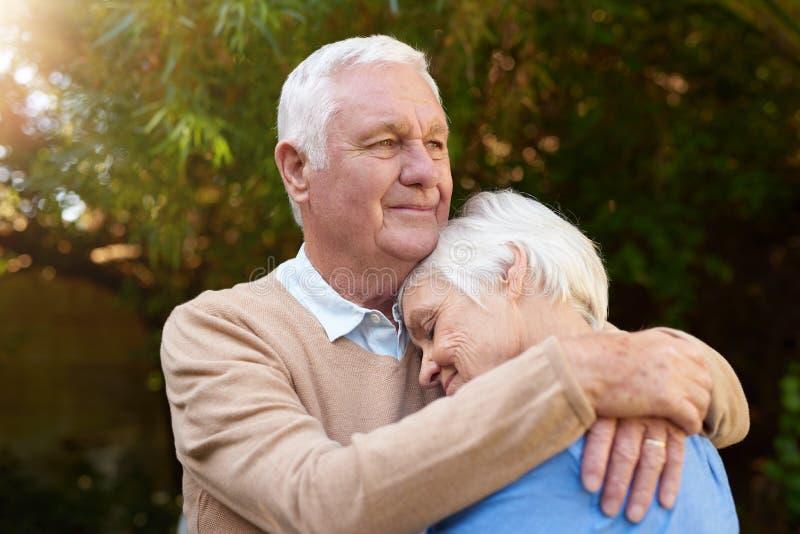 Uomo senior sorridente che abbraccia affettuoso la sua moglie fuori fotografie stock libere da diritti