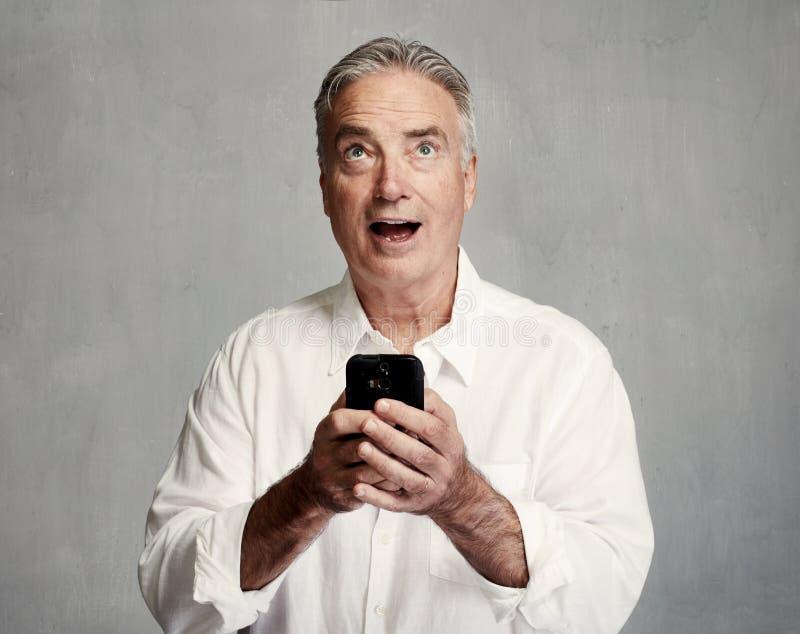 Uomo senior sorridente con lo smartphone fotografia stock libera da diritti