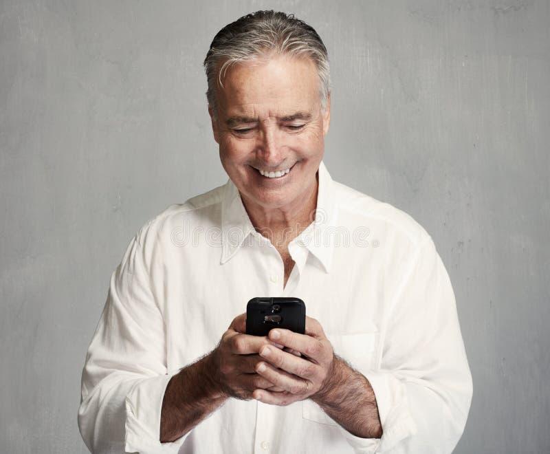 Uomo senior sorridente con lo smartphone fotografie stock