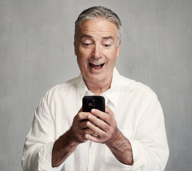 Uomo senior sorridente con lo smartphone fotografie stock libere da diritti