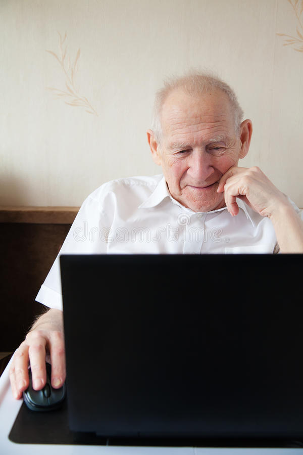 Uomo senior sorridente in Front Of il computer portatile immagini stock
