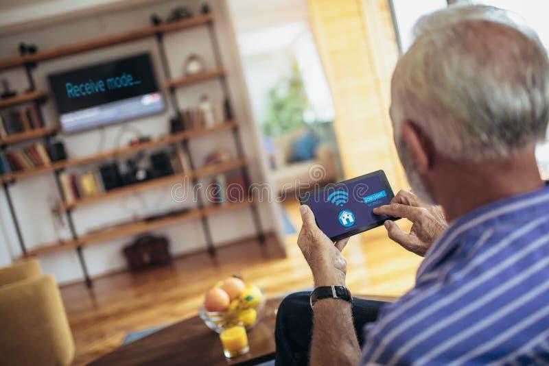 Uomo senior su un sofà che tiene il sistema di controllo domestico a distanza su una compressa digitale immagini stock libere da diritti