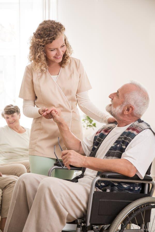 Uomo senior sulla sedia a rotelle con l'infermiere che tiene la sua mano immagini stock