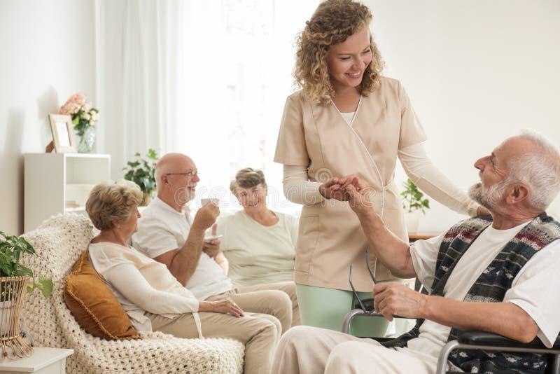 Uomo senior sulla sedia a rotelle con l'infermiere utile che tiene la sua mano immagine stock libera da diritti