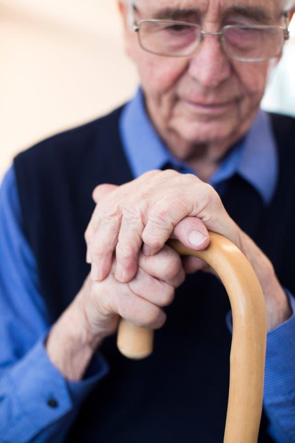Uomo senior triste che si siede in canna di camminata della tenuta della sedia fotografie stock