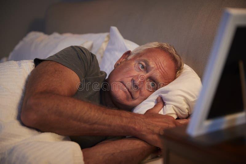 Uomo senior triste che si trova a letto esaminando la struttura della foto fotografie stock libere da diritti