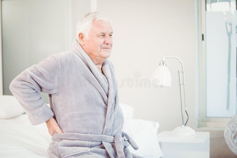 Uomo senior turbato che si siede con il dolore alla schiena sul letto immagini stock libere da diritti