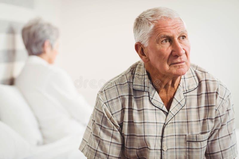 Uomo senior turbato che si siede sugli estremi opposti del letto fotografia stock
