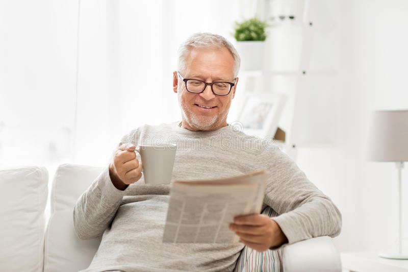 Uomo senior in vetri che legge giornale a casa fotografie stock libere da diritti