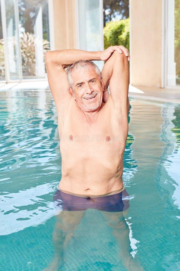 Uomo senior vitale che fa un esercizio d'allungamento nella forma fisica dell'acqua immagini stock